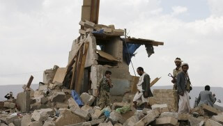 Houthi militants stand on the rubble of a house destroyed by a Saudi-led air strike in Yemen's capital Sanaa August 26, 2015. REUTERS/Khaled Abdullah