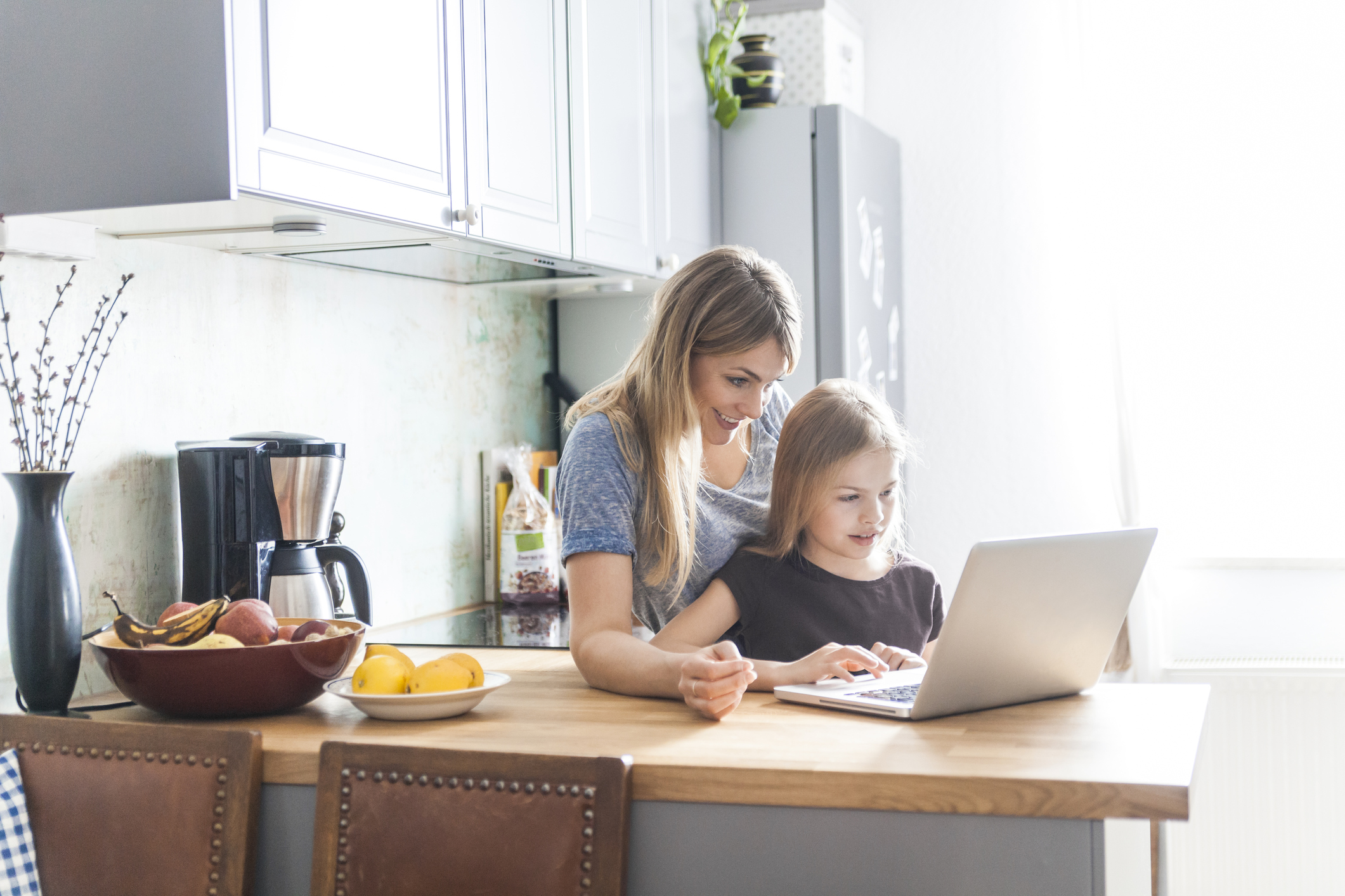 Keeping your kids safe online: Mother and daughter using laptop in kitchen