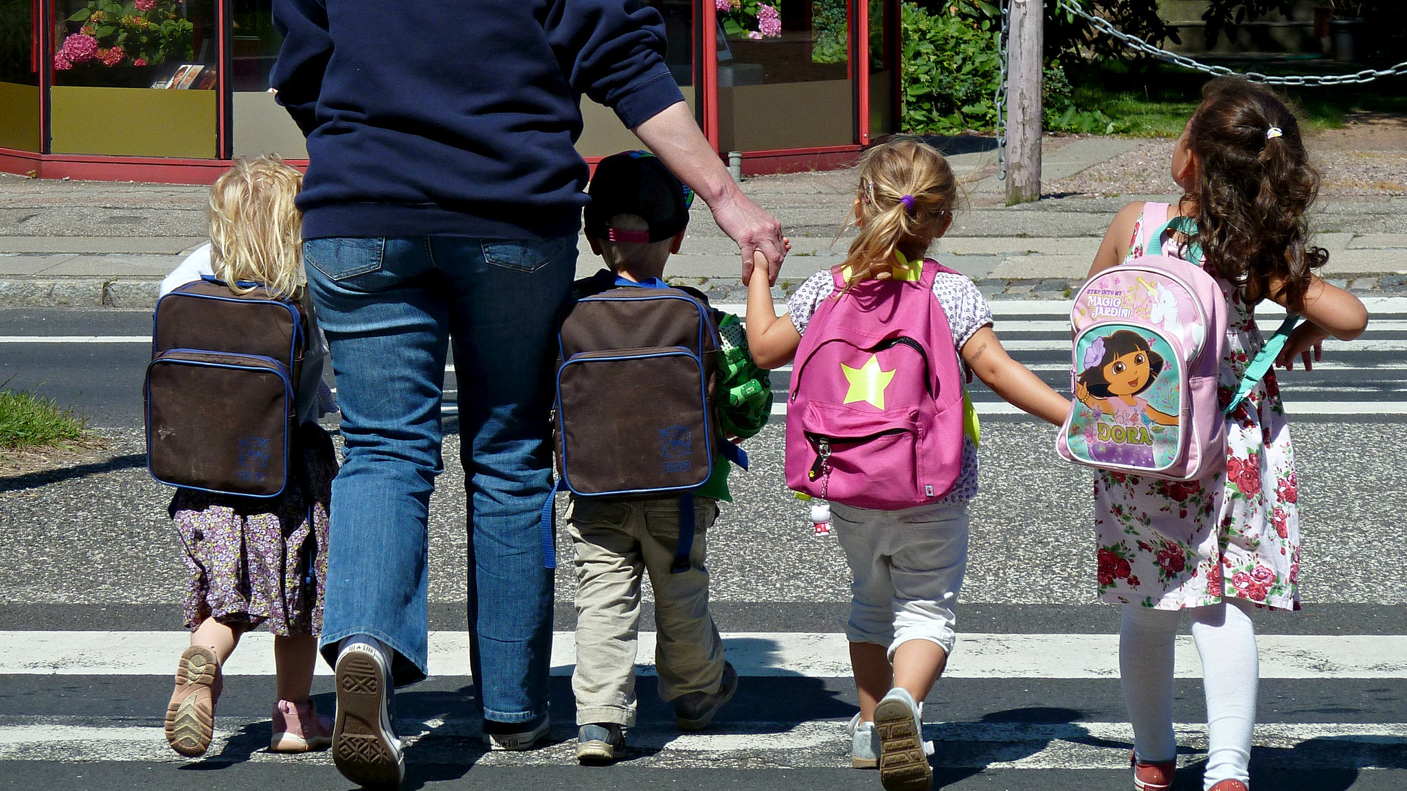 Helping kids cope with separation anxiety in the school setting: Kids with backpacks walking with an adult on the crosswalk