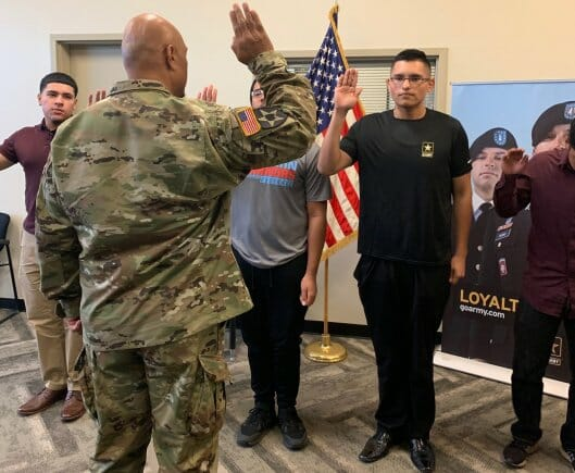Luis Enrique Pinto Jr., second from the right, takes the Oath of Enlistment after he lost 113 pounds in seven months in order to pass the Army's weight requirements.