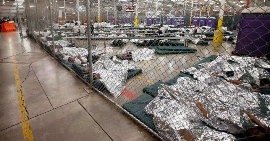 Detainees sleep and watch television in a holding cell where hundreds of mostly Central American immigrant children are being processed and held at the U.S. Customs and Border Protection Nogales Placement Center in Nogales, Arizona, on June 18, 2014.